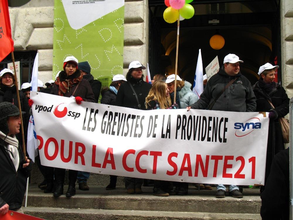 """Demonstration während des Streiks bei La Providence. Auf dem Transparent steht: """"Die Streikenden von La Providence. Für den Tarifvertrag Santé 21"""""""