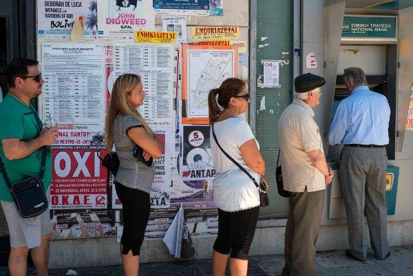 """Am Tag des Referendums bilden sich lange Schlangen vor den Geldautomaten. Genug Zeit, die Plakate im Hintergrund zu betrachten, die für ein """"Nein"""" bein bei der Abstimmung werben."""